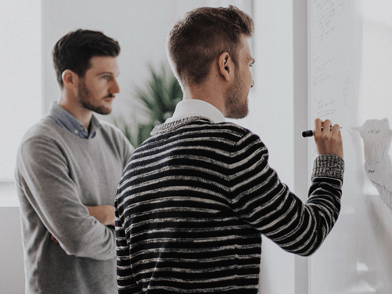 Customized Training - Man Demonstrating Theory on Whiteboard