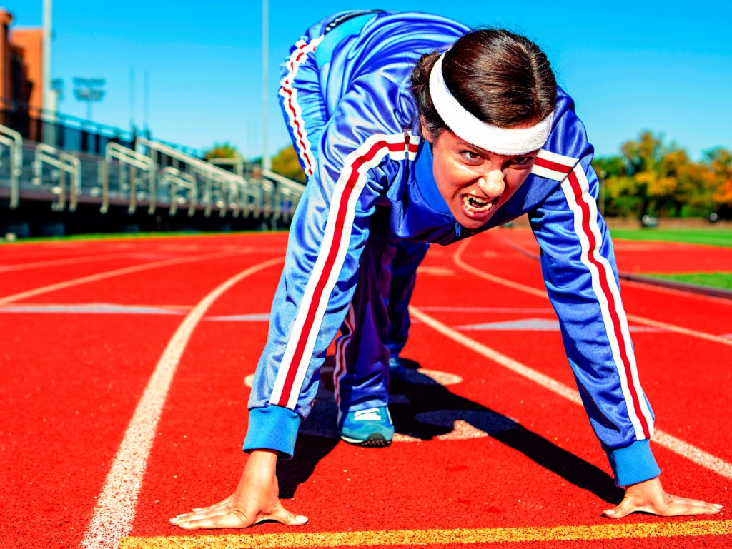 determined woman in track suit on running track starting line
