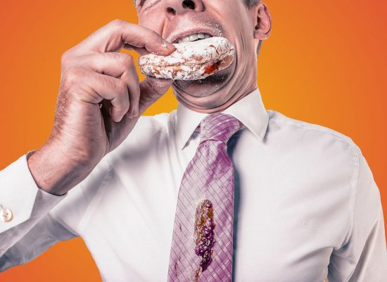 business man biting into jelly donut and jelly has landed on his tie